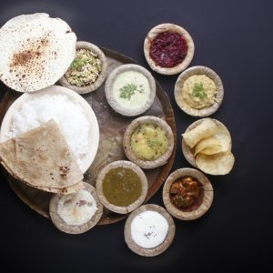 indian food with chapatti rice curries vegetables papad pickle payasam f4